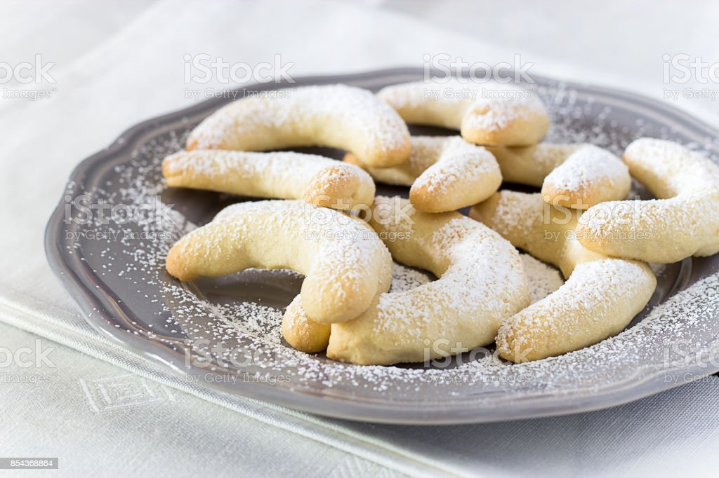 Traditional German Christmas cookies Vanilla Crescent Vanillakipferl with icing poweder on gray plate. Close up. Selective focus. White background. stock photo