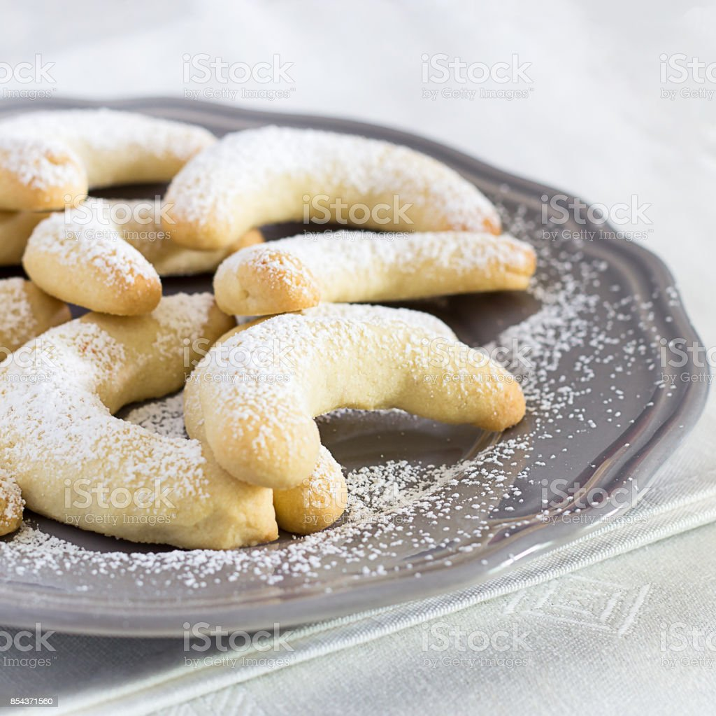 Traditional German Christmas cookies Vanilla Crescent Vanillakipferl with icing poweder on gray plate. Close up. Selective focus. Square photo stock photo