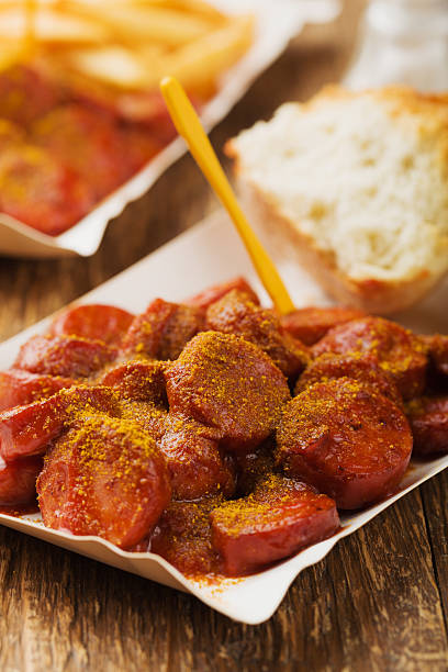 traditional german currywurst, served on disposable paper tray w - currywurst stock-fotos und bilder
