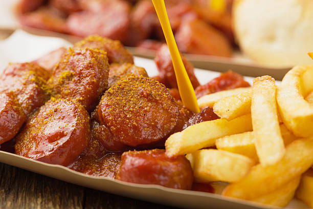traditional german currywurst, served with chips on disposable p - currywurst stock-fotos und bilder
