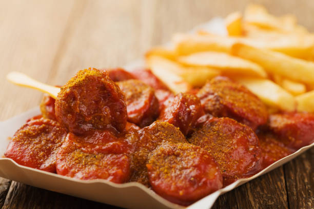 traditionelle deutsche currywurst, serviert mit chips auf einweg-papierblechen. - currywurst stock-fotos und bilder