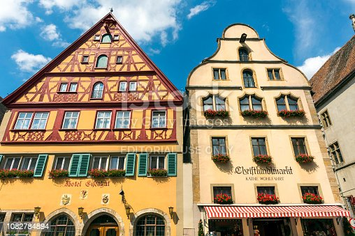 Rothenburg Ob Der Tauber, Germany - August 17, 2018: Traditional German houses with Sardinia flowers in Rothenburg ob der Tauber, Bavaria, Germany. Market Place of the historic old town Rothenburg ob der Tauber with Rathaus buildings in summer. Rothenburg ob der Tauber is a famous town in Bavaria, west of Munich, Germany. This old bavarian city is situated on the Romantic Road. Rothenburg ob der Tauber is a UNESCO World Heritage site