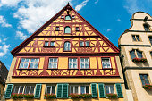 Rothenburg, Germany - August 17, 2018: Traditional German houses with Sardinia flowers in Rothenburg ob der Tauber, Bavaria, Germany.