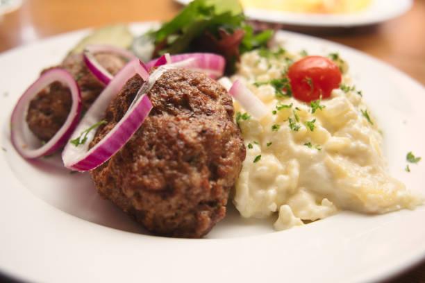 mit kartoffelsalat serviert traditionelle deutsche frikadellen () - frikadelle stock-fotos und bilder