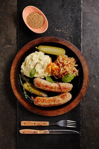 traditionelle deutsche würstchen mit kartoffelpüree und sauerkraut - bratwurst mit sauerkraut stock-fotos und bilder