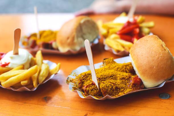 traditionelle gerichte der deutschen straße - currywurst, stücke von currywurst, serviert mit chips, pommes frites auf einweg-papierfach auf einem holztisch als hintergrund - currywurst stock-fotos und bilder