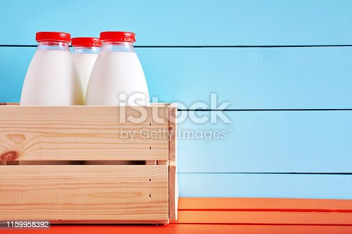 Milk bottles in a wooden crate on wooden kitchen table with blue wooden background. Close up view with copy space