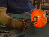traditional glassblowing worker cutting liquid glass