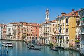 Traditional gondolas and touristic boat at the Grande Channel of Venice. Veneto, Italy.