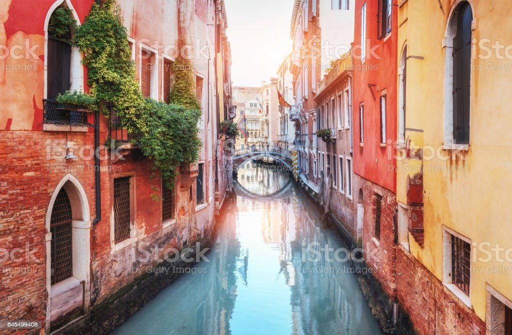 Traditional Gondolas on narrow canal between colorful historic houses in Venice Italy stock photo