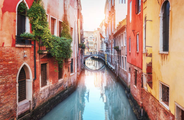 traditional gondolas on narrow canal between colorful historic houses in venice italy - karte venedig stock-fotos und bilder