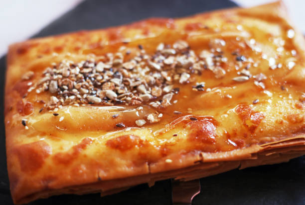 traditional greek cheese called feta - wrapped in phyllo crust - with honey, sesame and nuts stock photo