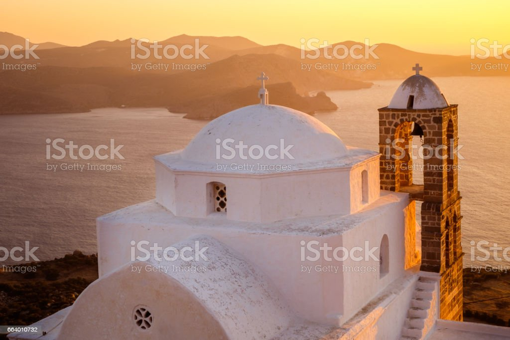 Traditional Greek church with ocean background at colorful sunset stock photo