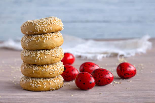 traditional greek easter cookies with sesame seeds and colored eggs - greek easter stock photos and pictures