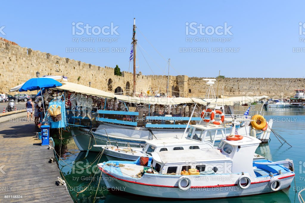 Traditional Greek fishing boats are staying moored at sea port of Rhodes town on Rhodes island, Greec stock photo