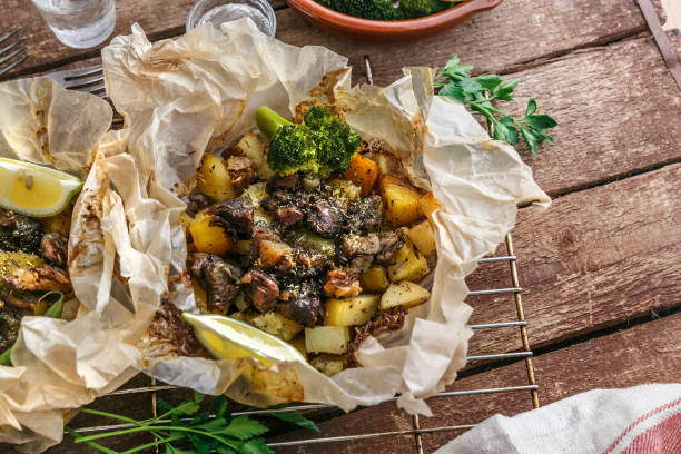 Traditional Greek kleftiko, an oven-baked lamb stew with potato, olive oil, onion, carrot, garlic and herbs, served with lemon and ouzo. stock photo