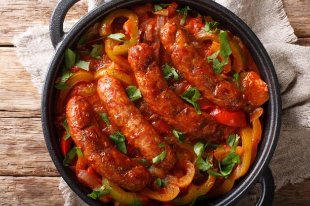 traditionell grillad korv med mångfärgad paprika, lök och tomater i närbild i en kastrull. horisontell vy uppifrån - korv bildbanksfoton och bilder