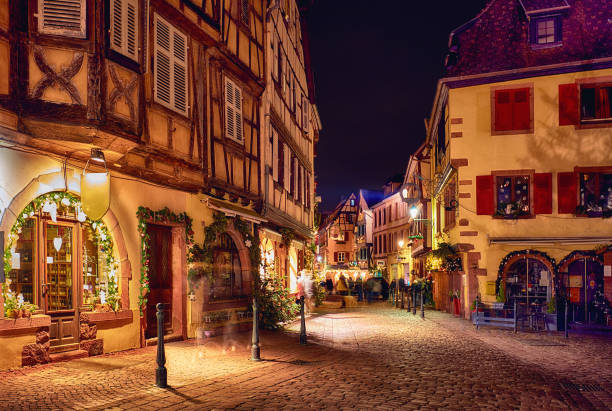 traditional half-timbered houses on narrow street of Kaysersberg, Alsace, France on Christmas eve stock photo