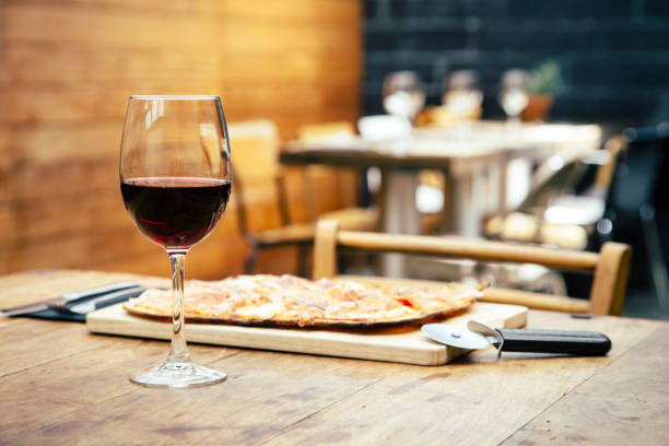 Traditional ham and brie cheese pizza with glass of red wine stock photo