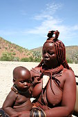 Epupa, Namibia - January 25, 2006: Himba woman with baby shows her traditional way of life, clothing, jewellery and headdress. The age and social status of a Himba can be seen in their hairstyle and jewelry. Married women wear an ornate headpiece.