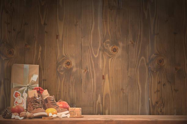 vacances traditionnelles saint nicolas - chaussures pour enfants remplies de cadeaux bonbons fruits et noix - fond en bois - saint nicolas photos et images de collection