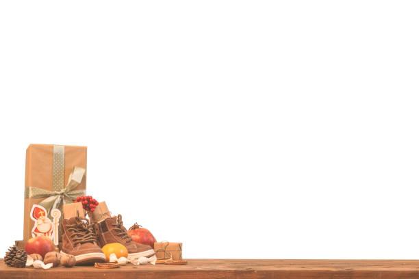 vacances traditionnelles saint nicolas ou sinterklaas - chaussures pour enfants remplies de cadeaux bonbons fruits et noix - isolésur le fond blanc - saint nicolas photos et images de collection