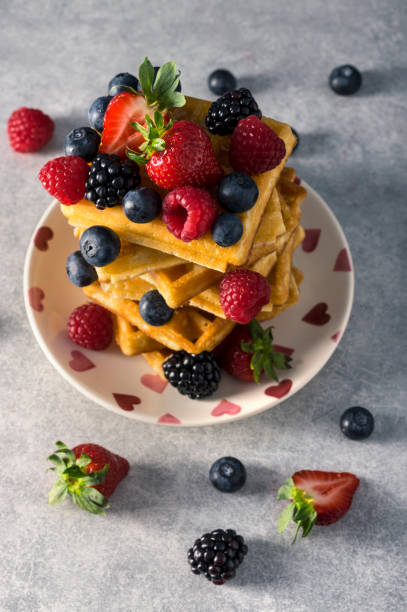Traditional homemade Belgian waffles with fresh summer berries, blueberry raspberry, strawberry and blackberry. Delicious breakfast. Selective focus. stock photo