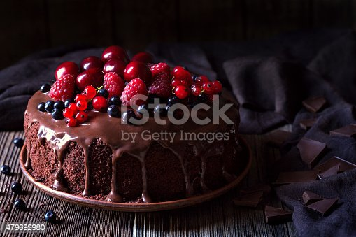 Traditional homemade chocolate cake sweet pastry dessert with brown icing, cherries, raspberry, currant on vintage wooden background. Dark food photo, rustic style, natural light.