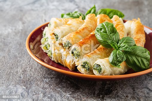 Traditional homemade Greek cheese, spinach pie on a red plate. Grey stone background