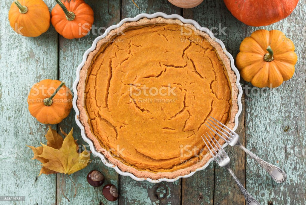 Traditional homemade open pumokin pie decorated with bright orange pumpkins and marple leaves on blue wooden background stock photo
