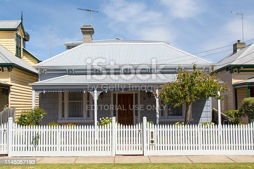 Williamstown, Australia: March 07, 2019: Traditionally built bungalow in the 20th century Australian style in Williamstown with a porch, ornate verandah, garden gate and white picket fence.