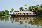 Traditional houseboat in the Kerala backwaters along palm tree coastline at a cloudless sunny day, Alappuzha, Alleppey, India