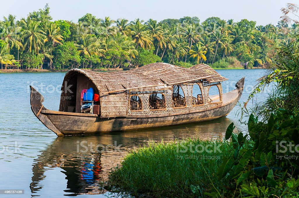 Traditional Houseboat of Kerala Backwaters on the river This shot was made in Backwaters of Kerala, India near Kochi. Backwaters in Kerala is a network of 1500 km of canals both manmade and natural, 38 rivers and 5 big lakes extending from one end of Kerala to the other. Backwaters is one of the major tourism product of Kerala, being unique to the state. Meandering through the coastal areas of Kerala is a 900 kilometers (560 miles) long intricate network of lagoons, lakes, canals, estuaries and deltas of several rivers that flow into the Arabian Sea. This is a natural phenomenon, as major rivers and streams that flows within Kerala drain themselves into backwaters regions, resulting in creation of several small land strips, lagoons, islands etc, which opens to sea at few areas. 2015 Stock Photo