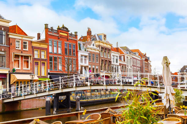 Traditional houses in downtown of Leiden, Netherlands Traditional dutch houses near canal, bridge and bicycles in downtown of Leiden, Holland leiden stock pictures, royalty-free photos & images