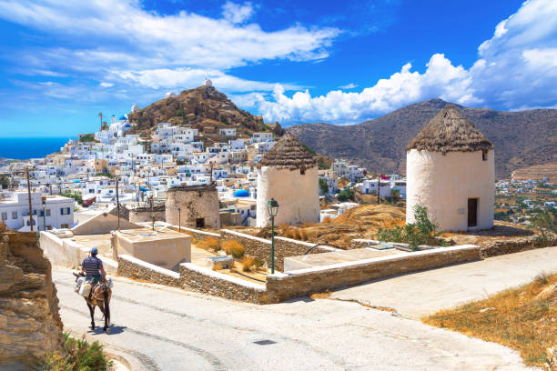 Traditional houses, wind mills, churches  and donkey in Ios island, Cyclades, Greece. stock photo