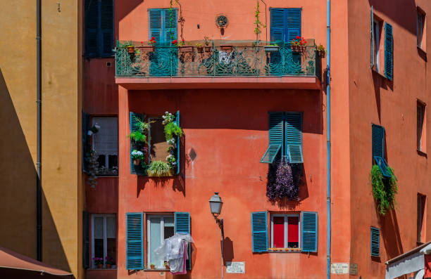 Traditional houses with ornate metal work and shutters in the streets of Old Town Vielle Ville in Nice, South of France stock photo