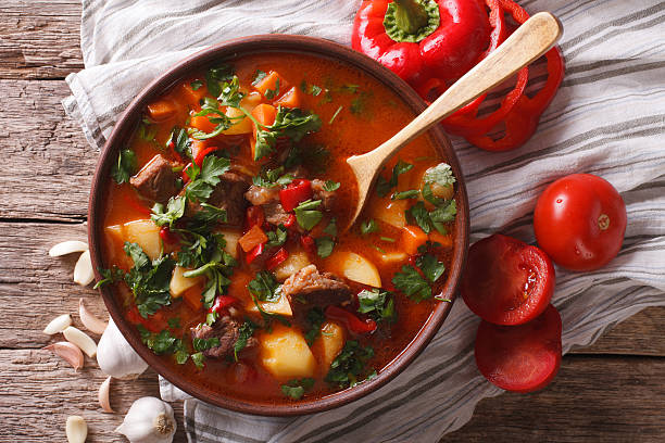 Traditional Hungarian goulash soup bogracs close-up in a bowl Traditional Hungarian goulash soup bogracs close-up in a bowl on the table. horizontal view from above stew stock pictures, royalty-free photos & images