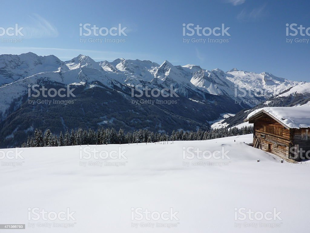 Traditional hut in the winter with mountains at background stock photo