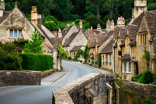 Color image depicting a traditional English village in the Cotswolds area of southwest England. The cosy little brick cottages line the narrow road, and there is also a quaint bridge spanning a little stream. Room for copy space.