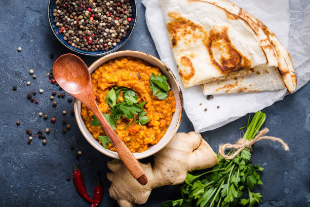 Traditional Indian lentils Dal Traditional Indian lentils Dal, naan butter bread. Space for text. Indian Dhal spicy curry in bowl, spices, herbs, rustic concrete background. Top view. Indian food. Authentic Indian dish. Copy space naan bread stock pictures, royalty-free photos & images