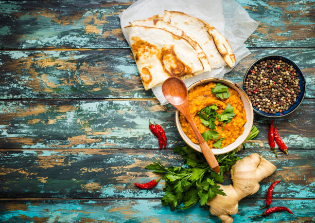 Traditional Indian lentils Dal Traditional Indian lentils Dal, naan butter bread. Space for text. Indian Dhal spicy curry in bowl, spices, herbs, rustic wooden background. Top view. Indian food. Authentic Indian dish. Copy space garam masala stock pictures, royalty-free photos & images