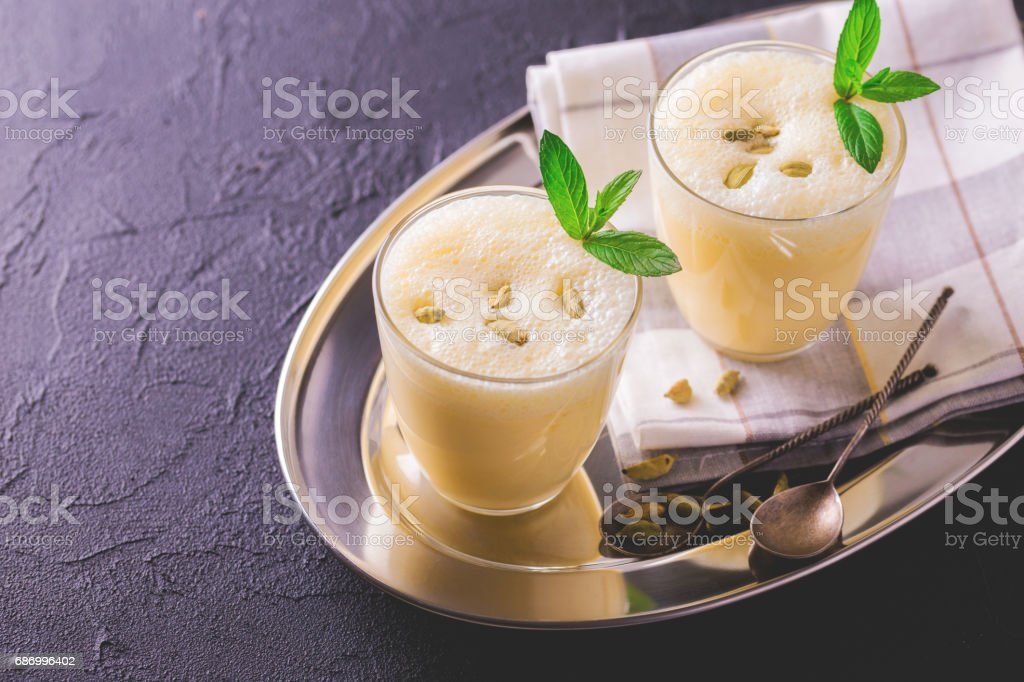 Traditional Indian mango lassi with cardamon, mint, vanilla and saffron Lizenzfreies stock-foto