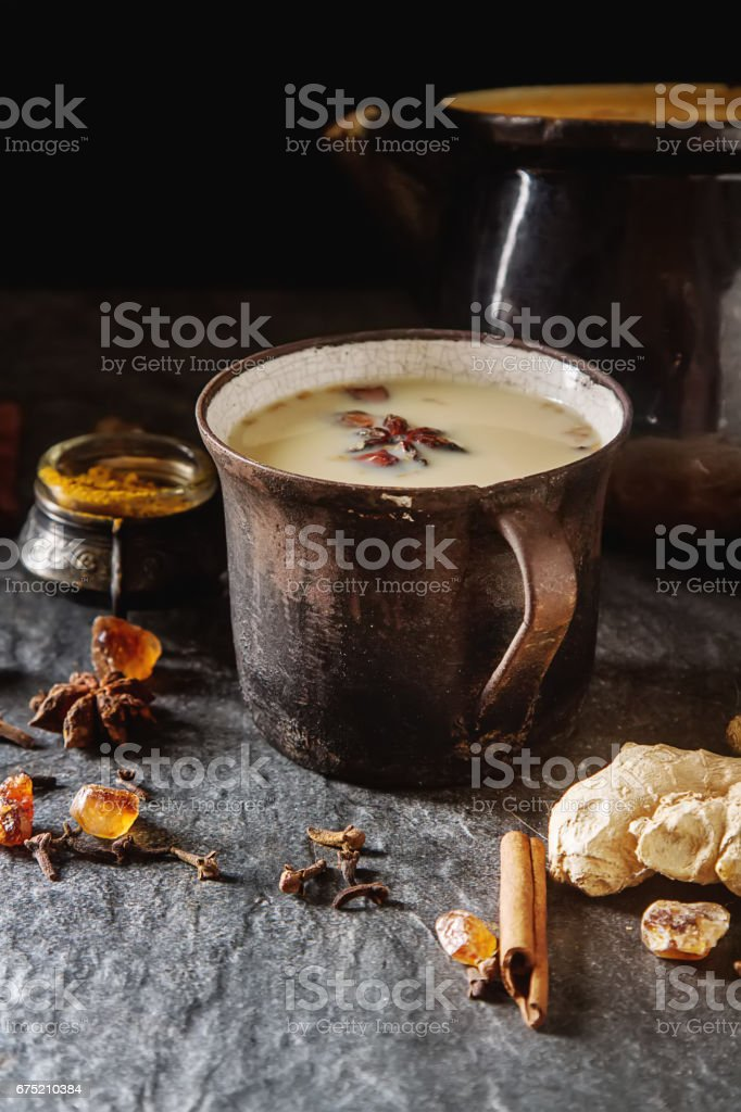 Traditional Indian masala tea in ceramic cup with spices to milk. Dark batskground. royalty-free stock photo