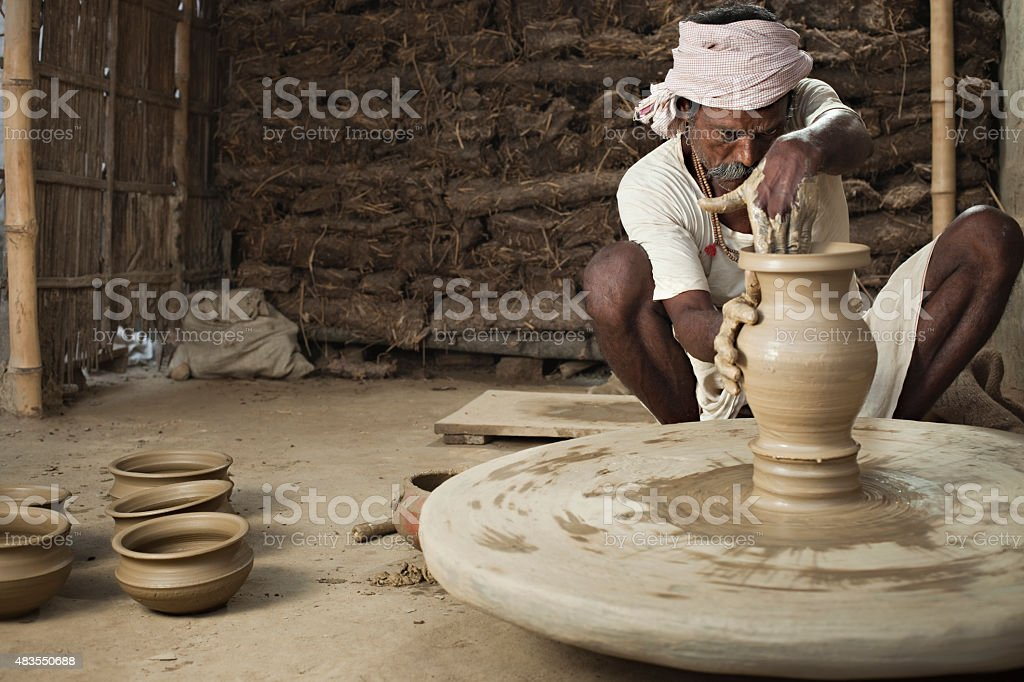 traditional indian potter making clay pot on manual pottery wheel stock photo more pictures of. Black Bedroom Furniture Sets. Home Design Ideas