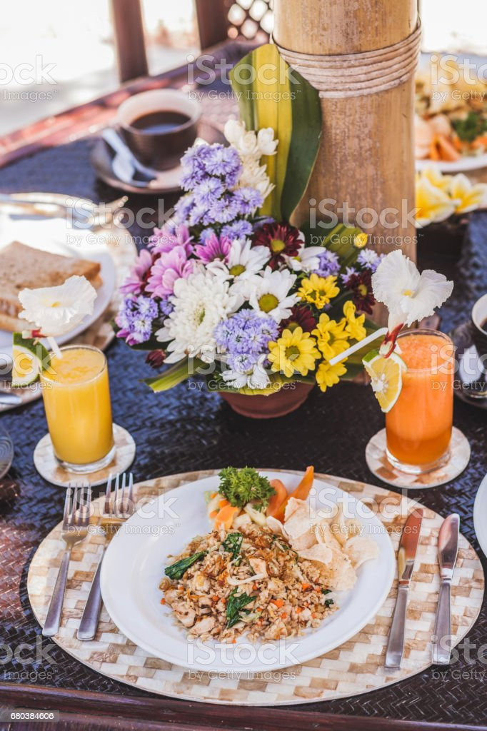 Traditional indonesian breakfast nasi goreng with bali kopi on white plate and silver cutlery on tray.  Table with different meals and fresh juices royalty-free stock photo