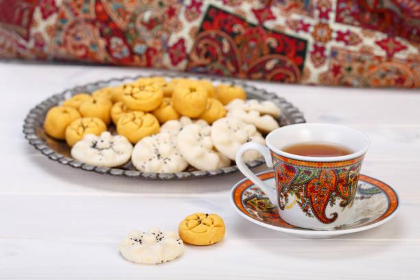 traditionelle iranische süßigkeiten runde form kichererbsen cookie gebäck und reis kekse im persischen toreutic platte mit einer nahaufnahme von paisley design tasse und untertasse tee auf weißem holz hintergrund - paisley kuchen stock-fotos und bilder