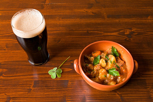 traditional irish stew and pint of beer and a shamrock - st patricks day food stock photos and pictures