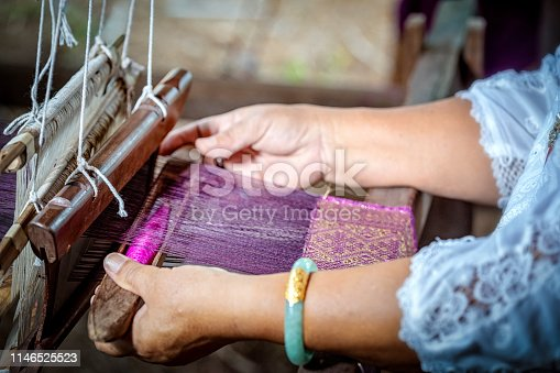 Traditional Isan Thai silk weaving. old woman hand weaving silk in traditional way at manual loom. Thailand . Selective focus.