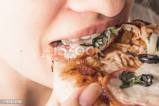 Traditional Italian appetizer - woman eats mini pizza, pizzetta with sausage, olives and mozzarella cheese, close-up bites mouth pizza