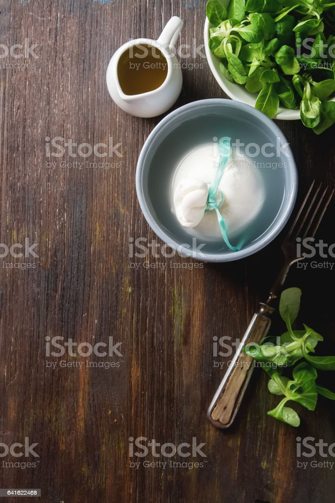 Traditional Italian cheese burrata, fresh salad, olive oil, in a stock photo